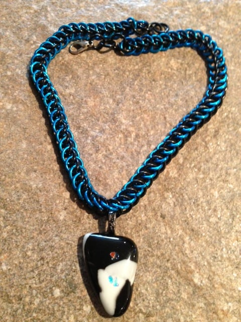 blue and black chainmaille weave  with a black and white fused glass pendant