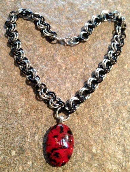 black and silver chainmaille weave with a red and  black fused glass pendant